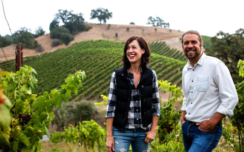 Couple smiling in front of vineyard