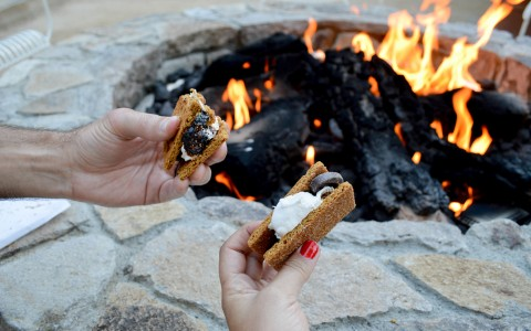 Couple holding smores next to fire pit