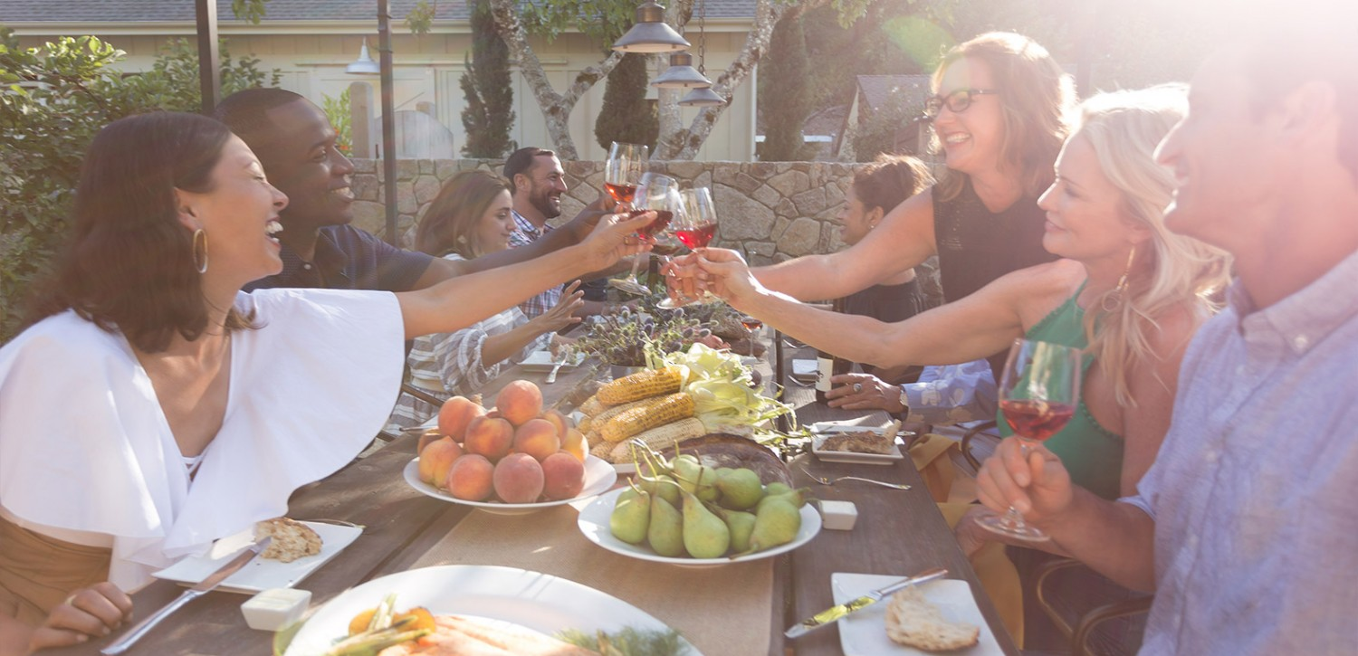 Group of friends laughing & toasting with wine at outdoor dining table