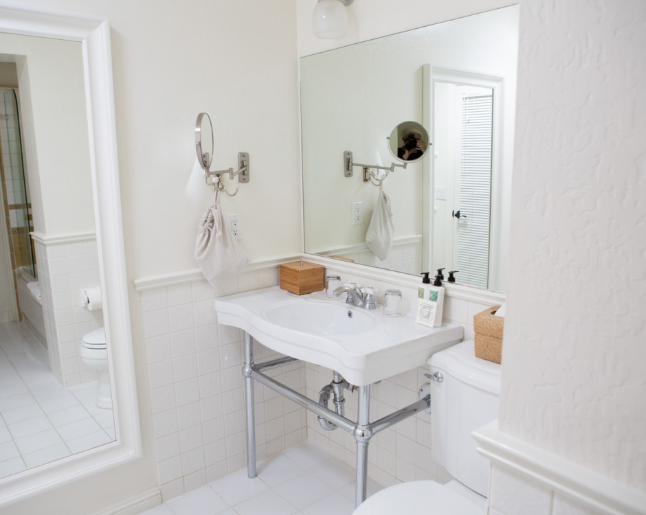 All white bathroom with sink & full body mirror on wall