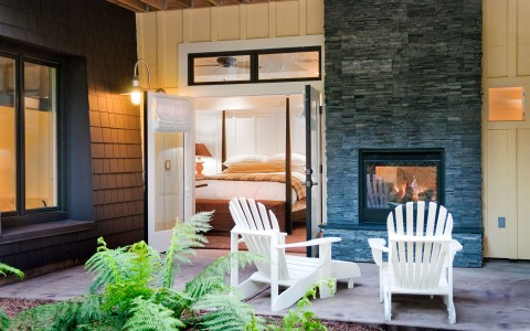 White lounger chairs on porch facing fireplace next to bedroom door