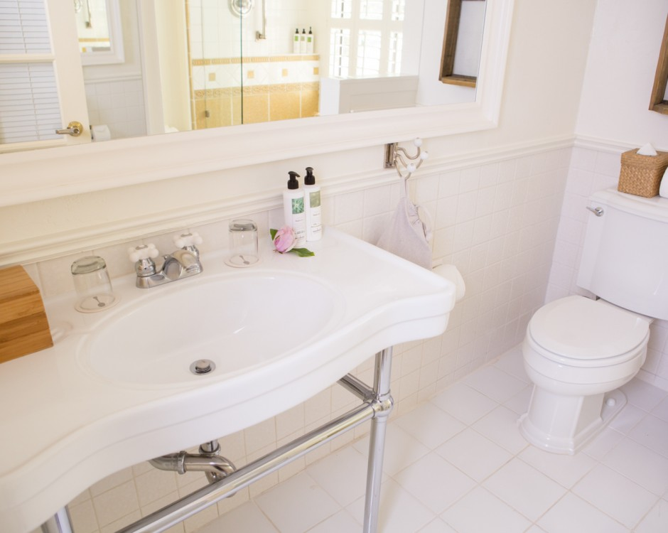 All white bathroom with sink, toilet & large mirror