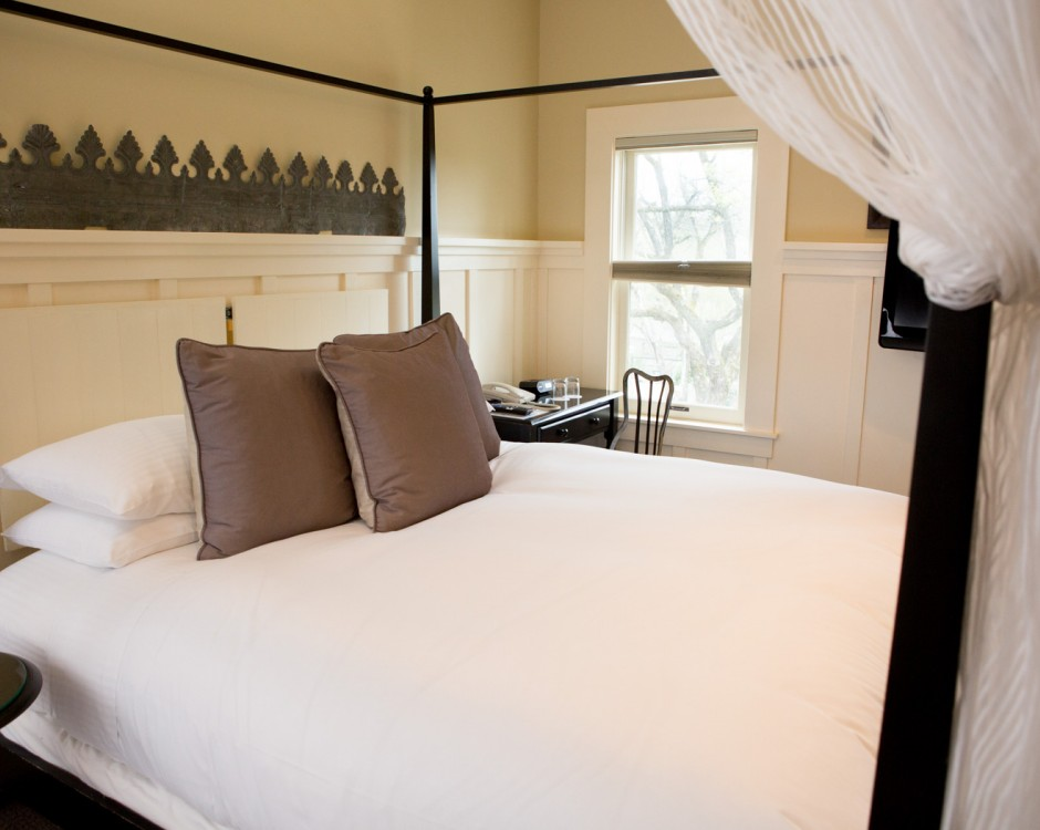 Room with king bed, white veil, wooden headboard & black desk