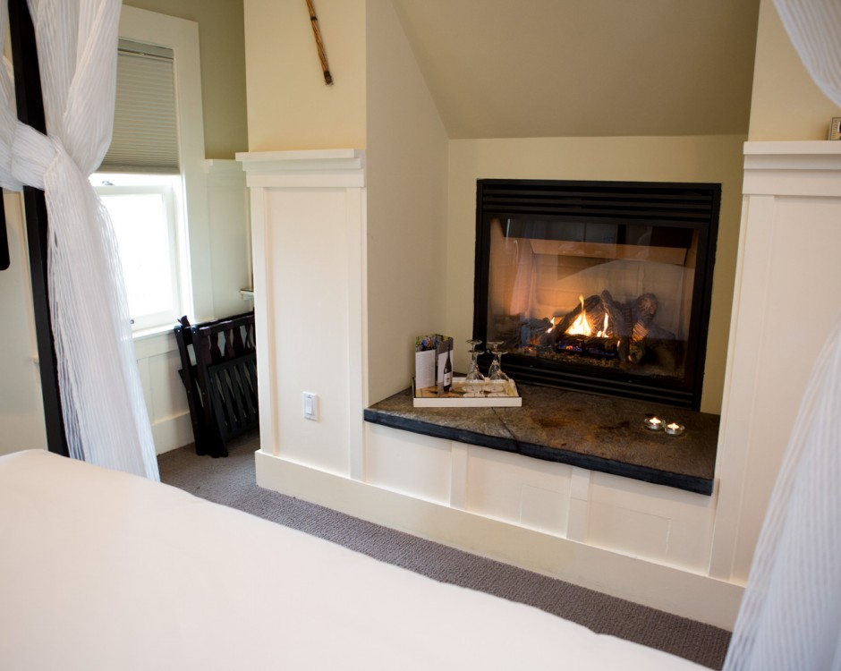 Bed with white veil next to fireplace & wine on tray
