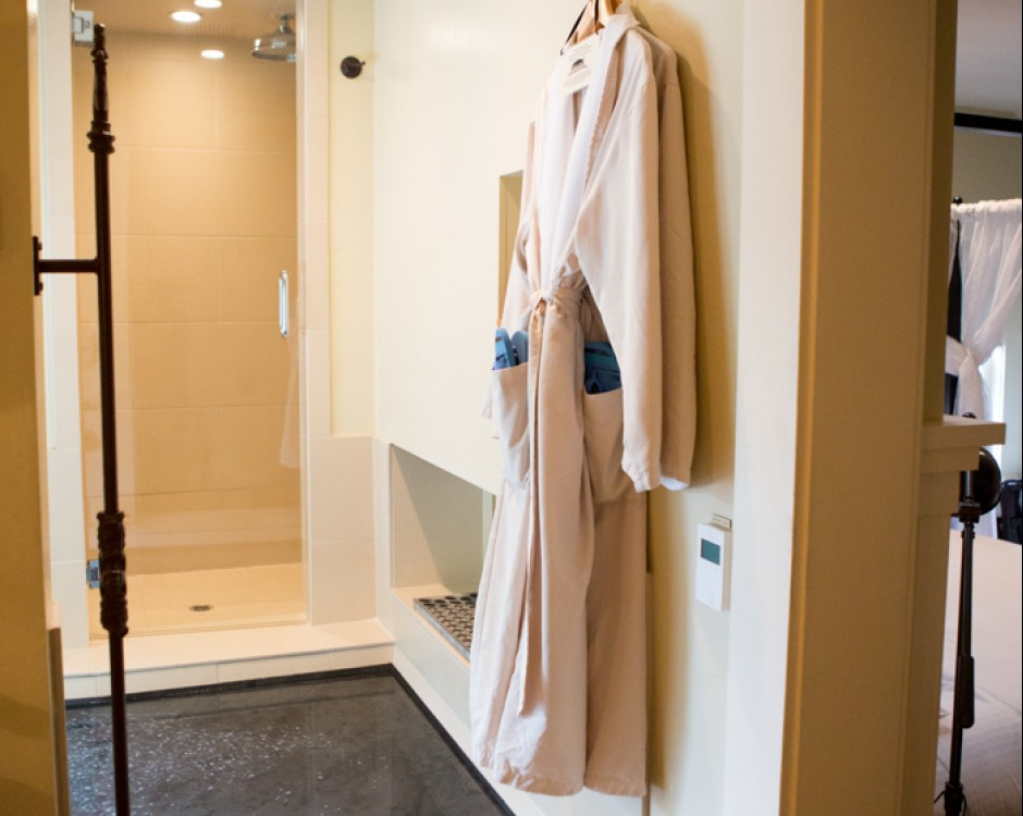 White robes hung next to tub filled with water