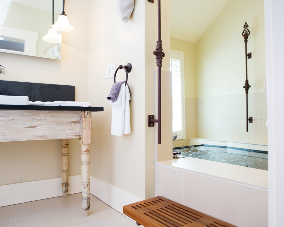 Bathroom with vanity & large tub with water pouring from ceiling
