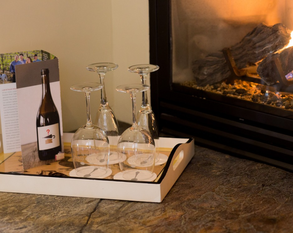 Wine glasses on tray next to fireplace