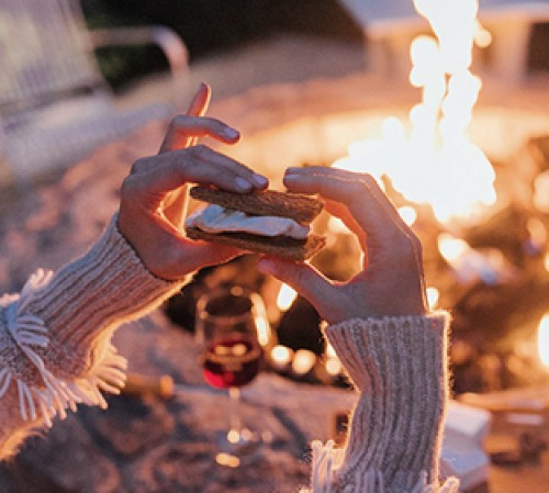 Woman holding smore by fire pit