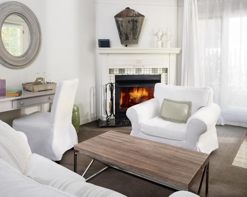 Living space with white couches, desk, mirror & fireplace in the back