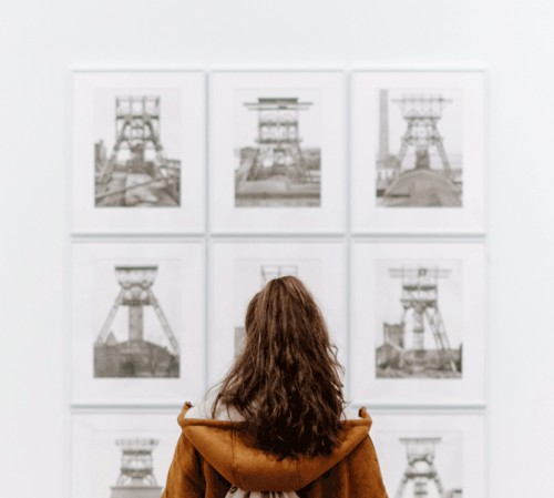Woman looking at sketches hung on wall at gallery