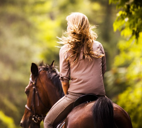 Woman horseback riding through forest