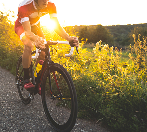 Man riding bike on trail during sunset