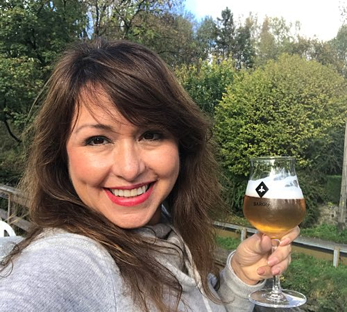 woman holding beer glass and smiling at the camera-1
