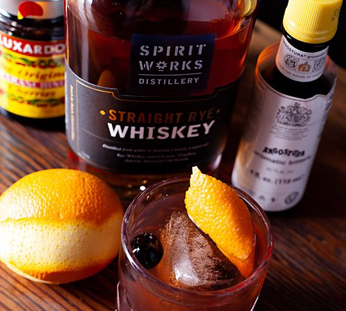 Spirit works whiskey next to low ball with orange in it-1