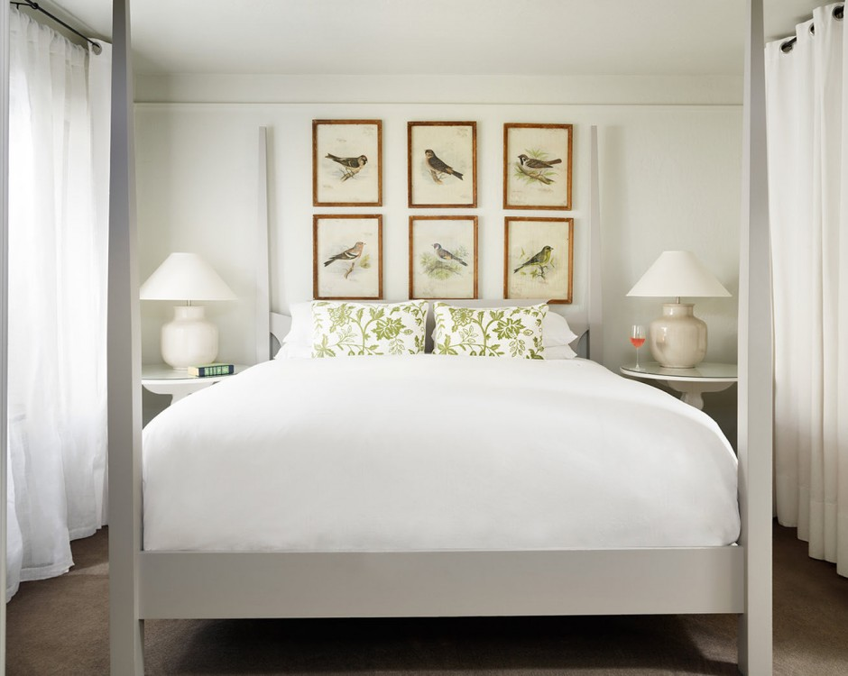 King bed with white linens and picture frames above the headboard