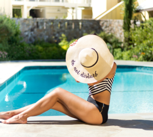 "Girl wearing hat with words ""do not disturb"" written on it, sitting in front of the pool"