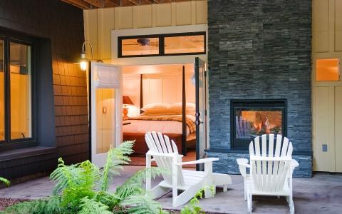 Exterior of king deluxe room with outdoor fireplace, chairs on terrace