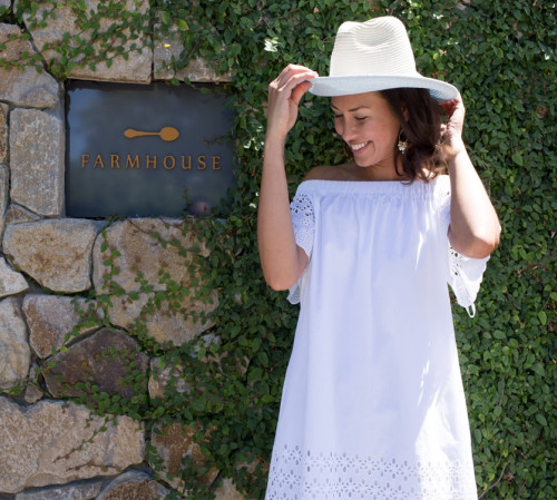 Woman standing in front of Farmhouse sign wearing white dress and white hat