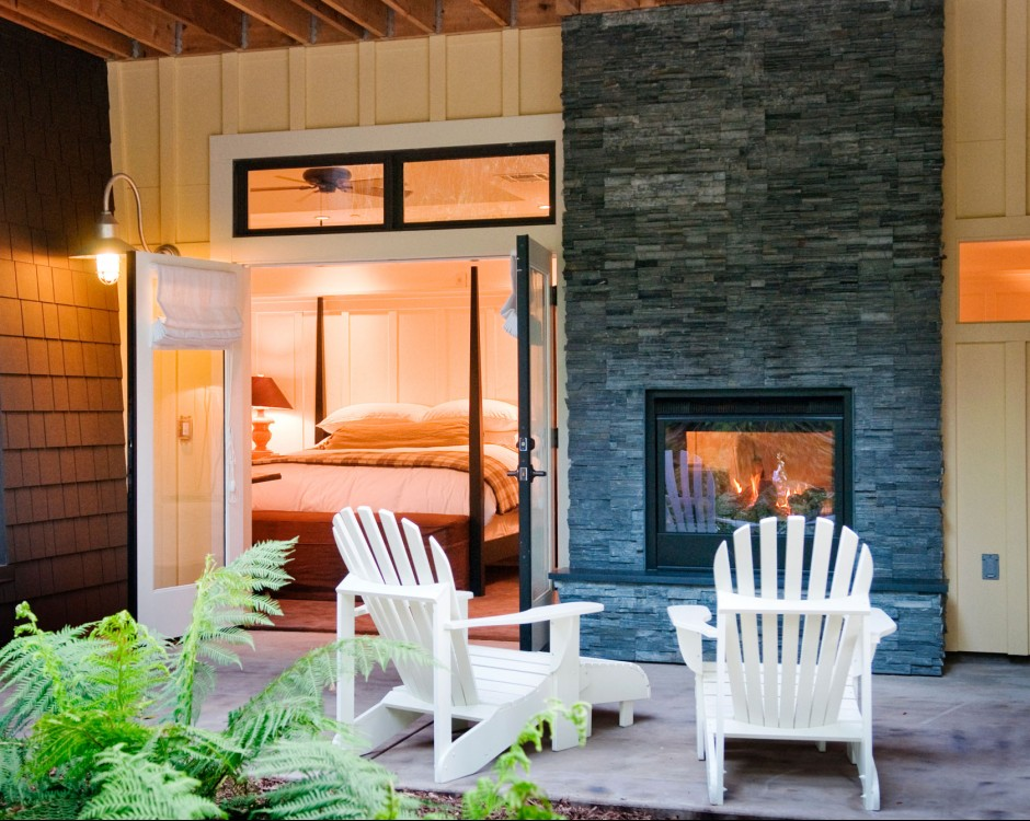 outside porch with white chairs and fireplace with room in background