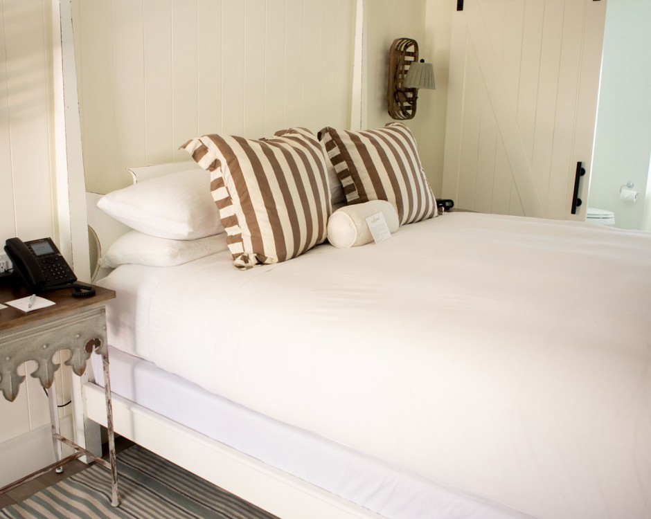 white bed with stripe accents on rug and bedding