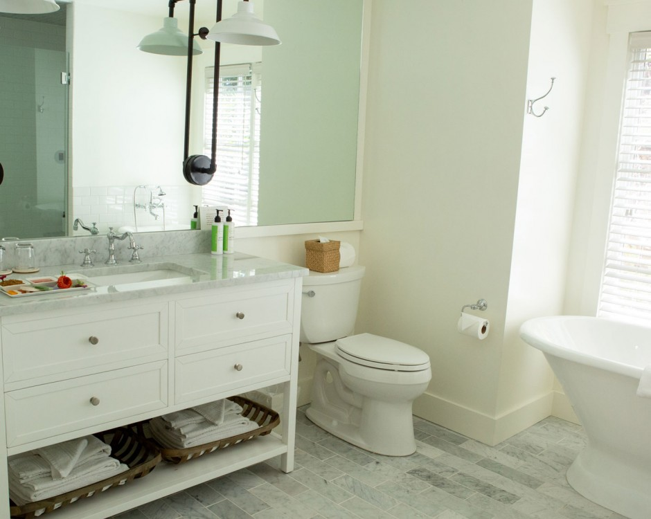 white modern bathroom with light fixtures and white claw bathtub