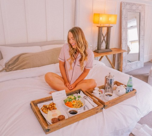 woman on bed with breakfast platters