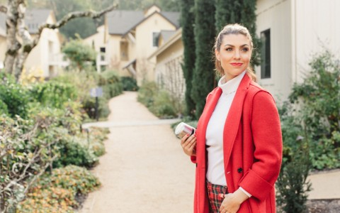 woman in a red coat standing on a path by green bushes