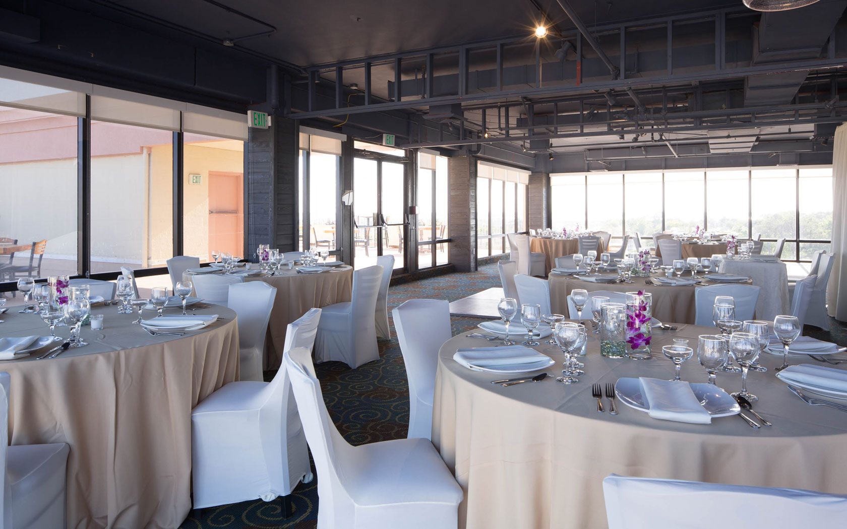 Event space housing several round tables with off white table clothes, covered chairs and formal dinner ware. Large glass wall opens to outdoor patio