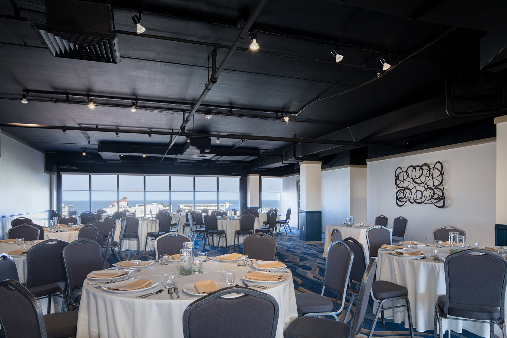 The Fenwick Room meeting space housing several round tables with white table clothes and formal dinner ware. Large glass wall opens to ocean view