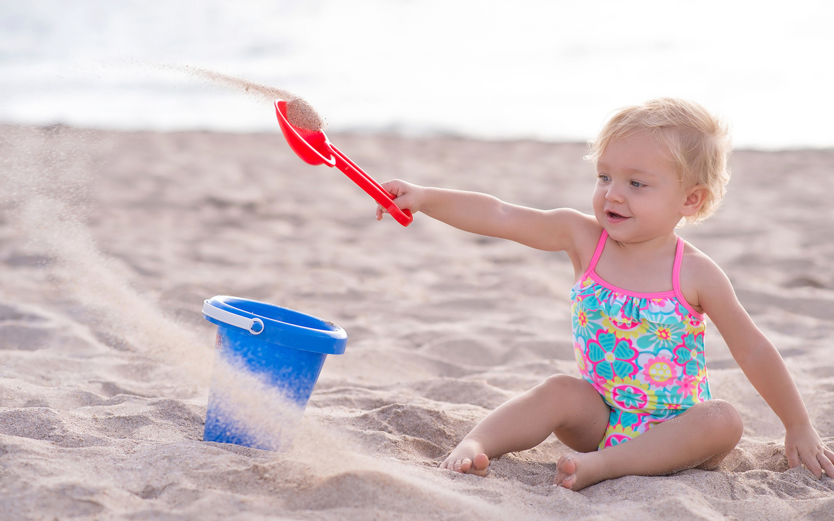 infant girl playing in the sand with a shovel and pale