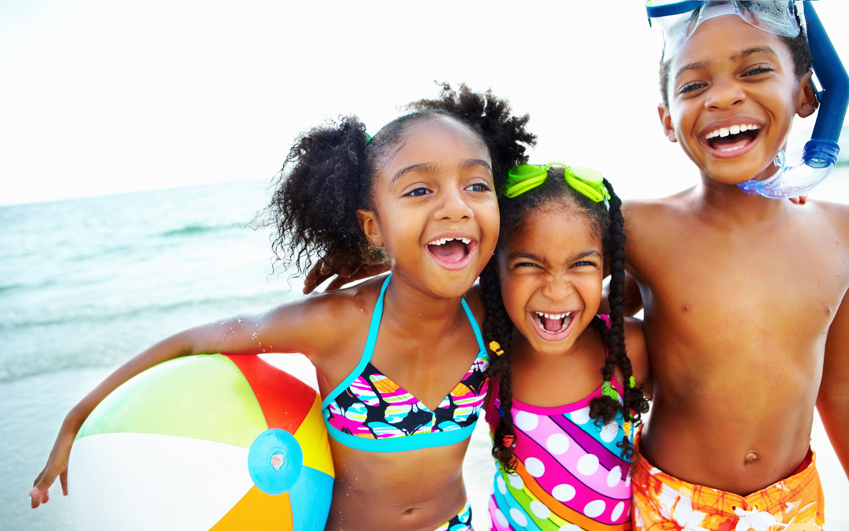 3 children on the beach, wearing bathing suits, sporting goggles and holding beach balls, laughing.