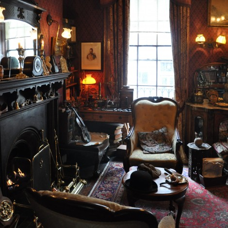 What appears to be a historic room of an old home. Outfitted with original furniture from 1800's appears to be a den with large chairs, fireplace, wall sconces