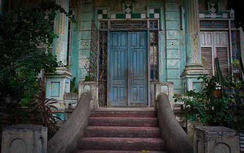 Blue door and cement steps of abandoned haunted house