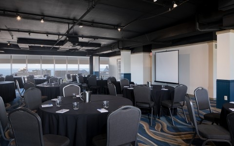 The Fenwick Room meeting space housing several round tables with no table clothes toped with notebooks, pens and a large projection screen at the front of the room. Large glass wall opens to ocean view