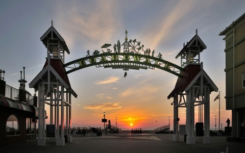 entrance to boardwalk with arch reading boardwalk and the sun setting in the background