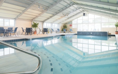 indoor swimming pool with lounge chairs and tables