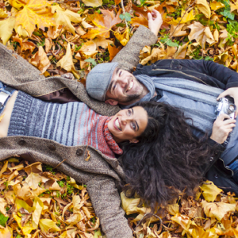 Cheerful couple laying in a pile of leaves
