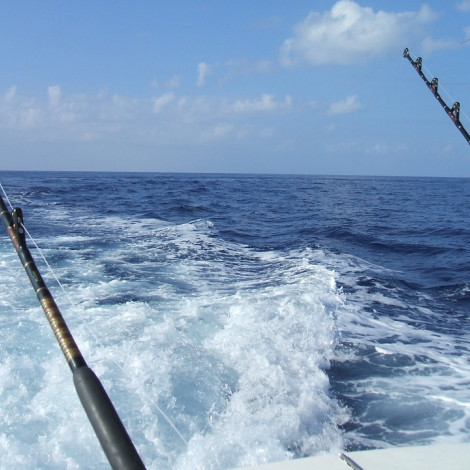 Two Fishing Reels on the ocean with white wake on blue water