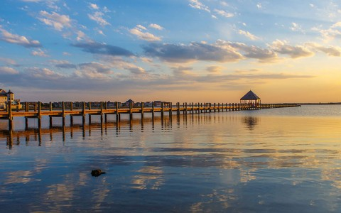 long beach and shoreline with pier during sunset
