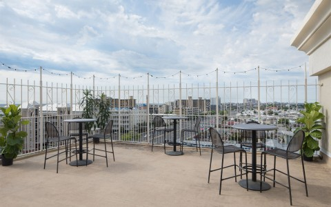 rooftop balcony with tall metal cafe tables panoramic city view . Wire rod iron fencing encloses space