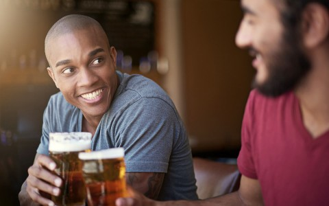 Two guys talking and drinking beer