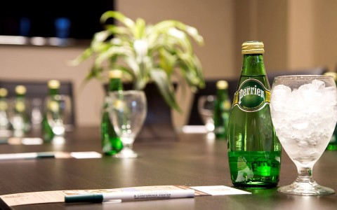 meeting table with glasses of ice and bottles of sparkling water