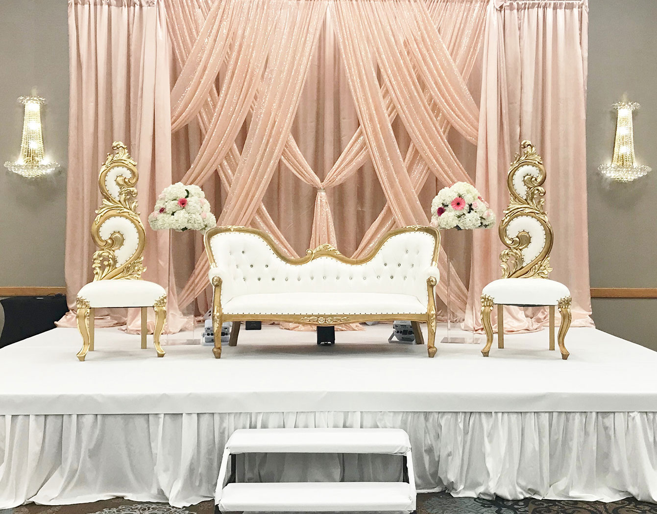 love seat with armchairs on both sides in front of creme draperies closeup