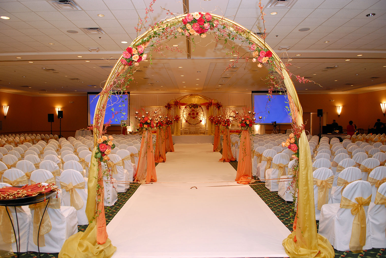 weddign ceremony set up with arch leading to the aisle with white chairs on both sides