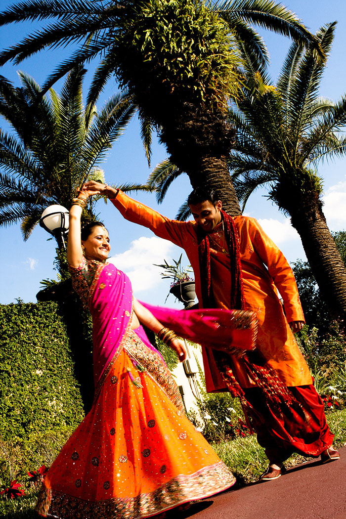 couple in extravagant ethnic clothes dancing outside in the sun
