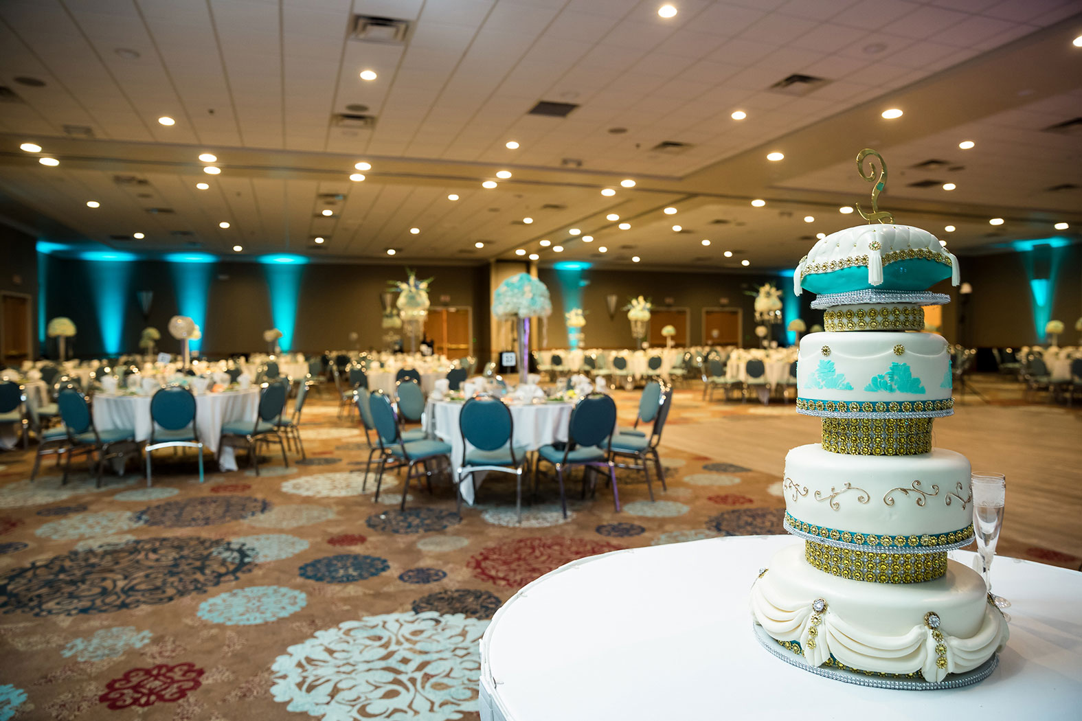 wedding reception set up with decorations and a four tier wedding cake