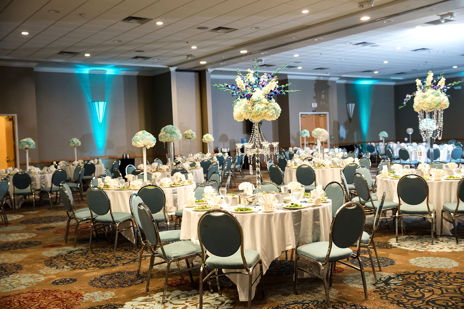 wedding reception setup with decorated tables and chairs