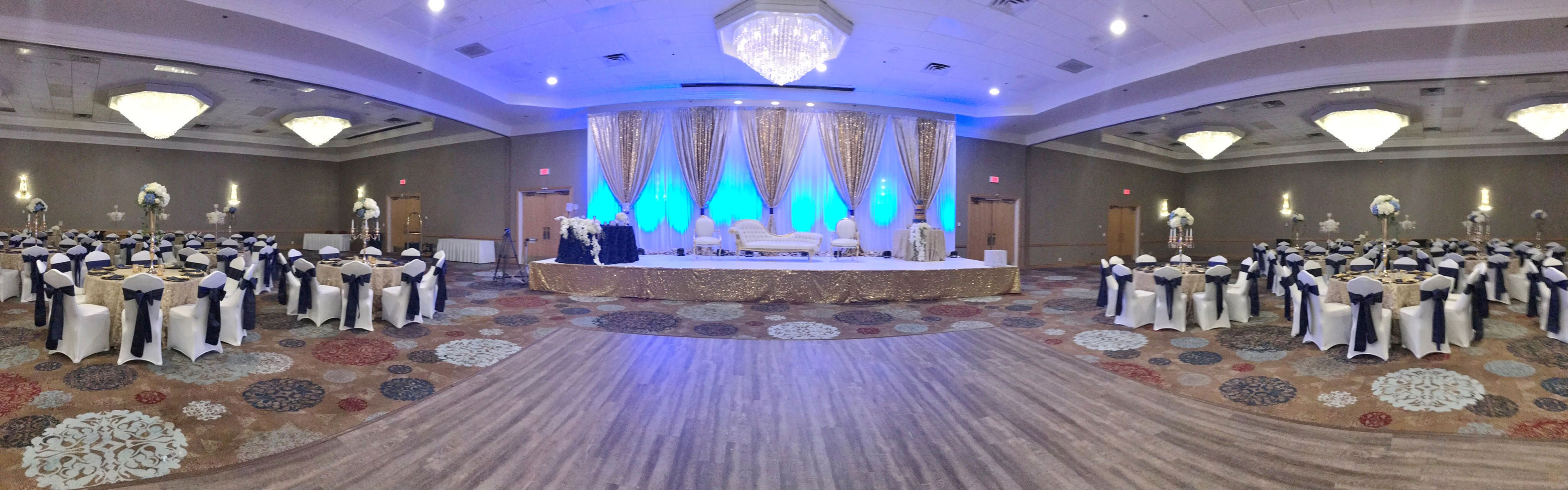 wedding reception set up with dance floor, lights, and flowers