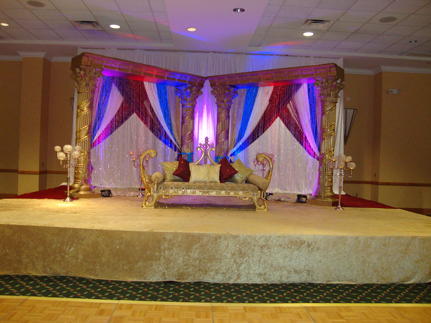 ethnic wedding setup with colorful curtains and a loveseat