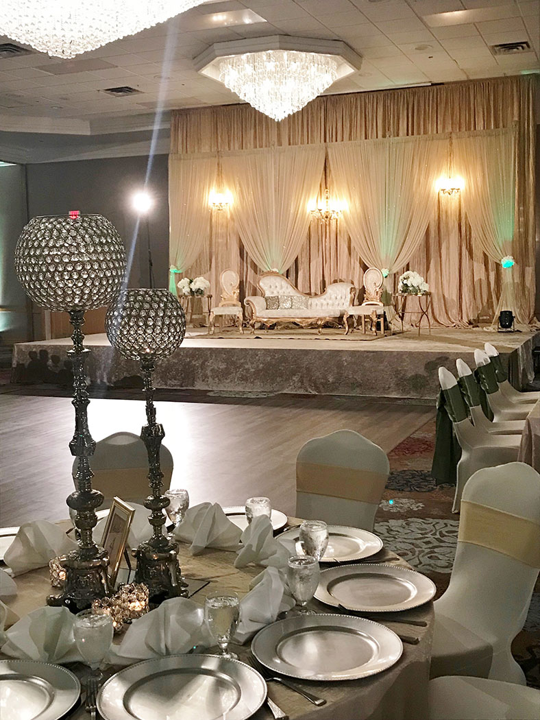 wedding reception set up with tables, chairs, decorations, and a stage